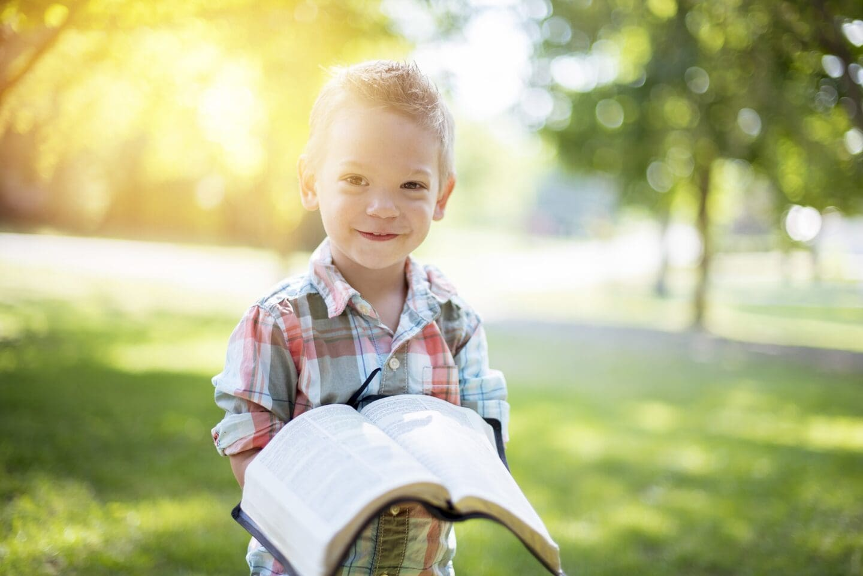 kid reading bible outside